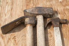 Old used hammers and adze. Old weathered grunge hammers and adze head closeup on plywood surface Royalty Free Stock Photo