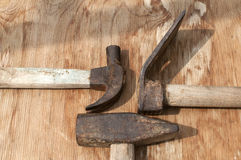 Old used hammers and adze. Old weathered grunge hammers and adze head closeup on plywood surface Royalty Free Stock Photos