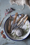 Old used kitchen knives and vintage strainer on plate on rustic table Stock Image