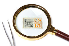 Old used postage stamp and magnifier Stock Image