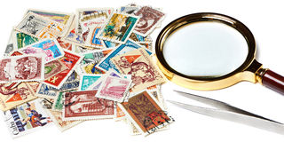 Old used postage stamps and magnifier Royalty Free Stock Photo