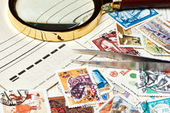 Old used postage stamps and magnifier Stock Image