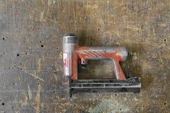Old used red air nailer or nail gun carpenter tools Stock Image