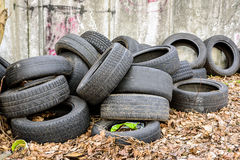Old used rubbish tires lies near the wall Royalty Free Stock Image