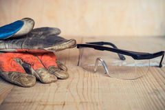 Old used safety glasses and gloves on wooden background Stock Photos