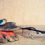 Old used safety glasses and gloves on wooden background Stock Images