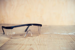 Old used safety glasses on wooden background Stock Image