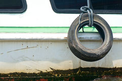 Old used tire with rope on the side of boat Royalty Free Stock Photo