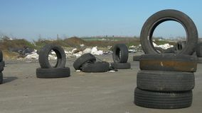 Old used tires are stacked on the paved road. A lot of debris in the background. Wind moves the pieces of trash. Bright sunny day. Old used tires are stacked on stock video footage