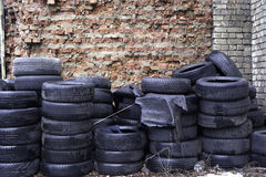 Old used tires stocked for recycling at red brick wall.  stock images
