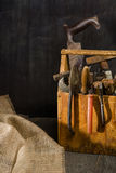 Old used tools in the toolbox. Dark background. spot lighting. Wooden box. Royalty Free Stock Images