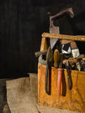Old used tools in the toolbox. Dark background. spot lighting. Wooden box. Stock Photos