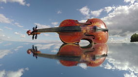 Old used violin music instrument on mirror and clouds. Art concept, timelapse 4K stock footage