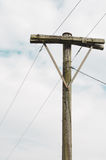Old utility pole with a cloudy sky. Stock Images