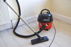 Old vacuum cleaner Henry with funny design in home interior.
