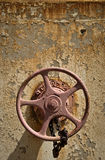 Old Valve Wheel. A painted metal wheel for controlling a valve sits locked on the exterior of an old factory Stock Photos