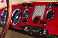 Old vehicle dashboard. A photo of an ancient red car dashboard with many buttons and mechanical displays Royalty Free Stock Photo