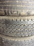 Old vehicle tyre close. Patterned tire used long ago stock photography