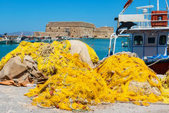 Old Venetian harbour. Crete, Greece. Fishing nets and fishing boats near Venetian fortress in the port of Heraklion. Crete, Greece Royalty Free Stock Photo