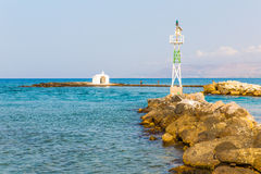 Old venetian lighthouse at harbor in Crete, Greece. Small cretan village Kavros. Royalty Free Stock Photos