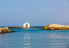 Old venetian lighthouse at harbor in Crete, Greece. Small cretan village Kavros. Royalty Free Stock Image
