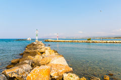 Old venetian lighthouse at harbor in Crete, Greece. Small cretan village Kavros. Royalty Free Stock Images