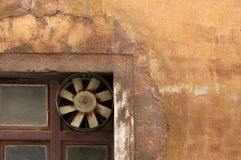 Old ventilation fan on decaying ochre wall. Detail of decaying, cracked, ochre facade with old ventilation fan royalty free stock photo