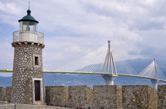 Old versus new, aged lighthouse versus modern cable bridge Stock Images