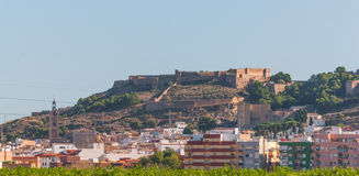 Old versus new. Castle in background, town in foreground from highway in rural Spain. Old home castle versus new modern town buildings. Small community living stock photography