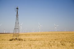 Old versus new windmills. Old windmill versus new windmills royalty free stock photos