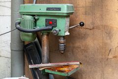 Old vertical green drilling machine with a big red power button and rust on the iron elements in an industrial production workshop royalty free stock photos