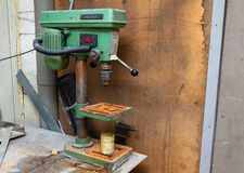 Old vertical green drilling machine with a big red power button and rust on the iron elements in an industrial production workshop stock image