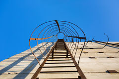 Old vertical industrial metal rusted ladder. Staircase to blue sky with clouds with safety rails and screens landings stock images