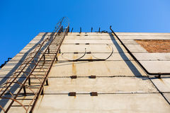Old vertical metal ladder. Old vertical industrial metal rusted ladder on the concrete wall. Staircase to blue sky with clouds with safety rails stock image