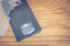 Old VHS Video tape cassette put on wooden table. Selective focus Royalty Free Stock Photography