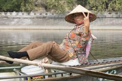Old Vietnamese lady on her sampan boat. Woman rowing her sampan boat with her feet. On the Tam Coc river you can go on a 2 hour boat ride where the rowers royalty free stock image