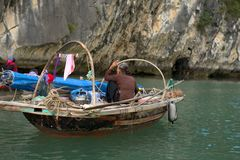 Old vietnamese woman rowing. Vietnamese woman in a hat seen rowing in ha long bay Stock Photos