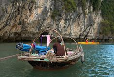 Old vietnamese woman rowing. Vietnamese woman in a hat seen rowing in ha long bay Stock Photography