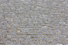 Old view of monotone gray brick stone on the ground for street road. royalty free stock images