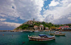 Old village. On the hill at seaside with fishing boats in foreground Royalty Free Stock Photo