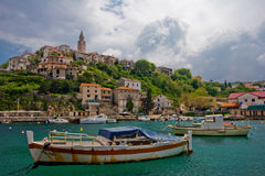 Old village. On the hill at seaside with fishing boats in foreground Stock Images