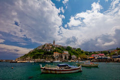 Old village. On the hill at seaside with fishing boats in foreground Royalty Free Stock Photography