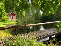 Old village building on the lakeside. Old Finnish home of wood on the lake stock photography