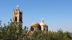 Old Village Church with Olive Tree and bell tower with blue sky. Panorama view over old village church and olive tree with bell tower and dome in north Cyprus Royalty Free Stock Image