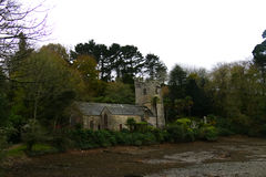 Old Village Church on river estuary. Winter view of Village church located on river bank estuary in Cornwall UK stock images