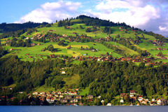 Old Village on Hill in Switzerland. A old style village in Switzerland on a hill with green trees and grass with homes and buildings next to a lake near Stock Photos