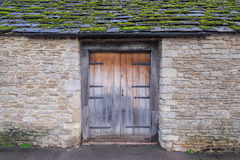 Old village house, with wooden door and moss covered roof Stock Photo