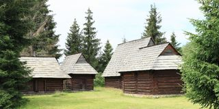 Old village houses in open-air museum. Old wooden village houses with shingles roofs among pine trees in open-air museum Liptov Village Museum Pribylina in Stock Photography