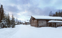Old Village Log Houses in museum Small Karelians near Arkhangelsk, Russia. Winter sunset time. Royalty Free Stock Image