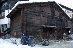 Old village with modern style. New bicycle with a trolley parked near the storehouse of 17th century. Old swiss village. Zermatt Stock Photo